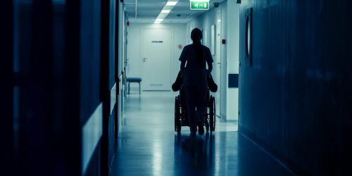 Silhouette of the Female Nurse Moving Patient in the Wheelchair in the End of Hospital Corridor. Doing Procedures. Bright Modern Hospital with Friendly Staff.